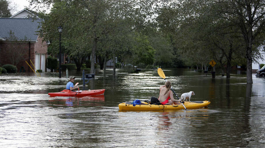 James Savage, left, and his girlfriend, Ianna Fincher, with her dog Lucy, kayak down Mayfield Street in the Ashborough subdivision near Summerville, S.C., after many of their neighbors evacuated Monday, Oct. 5, 2015. South Carolina is still struggling with flood waters due to a slow moving storm system. (AP Photo/Mic Smith)