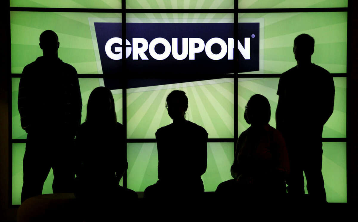 FILE - In this Sept. 22, 2011 file photo, employees at Groupon pose in silhouette with the company logo in the lobby of the online coupon company's Chicago offices. Websites like Groupon have become the go-to place for folks looking for that half-off deal on a manicure, a two-for-one offer for a fancy dinner or that all-inclusive trip that won?'t break the bank. But increasingly, it?'s also becoming the place for music fans to scoop up deep discounts on concert tickets and CDs of top-name acts. (AP Photo/Charles Rex Arbogast, File)