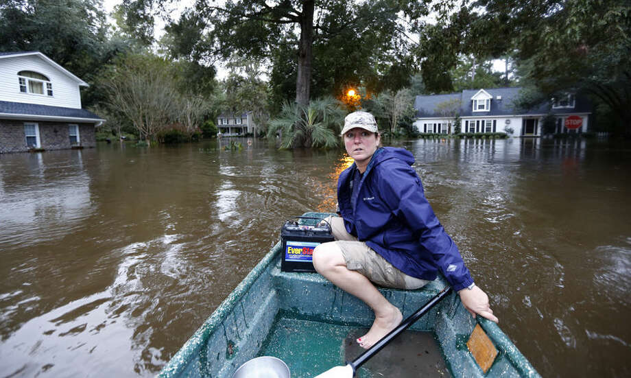 Jeanni Adame rides in her boat as she checks on neighbors seeing if they want to evacuate in the Ashborough subdivision near Summerville, S.C., after many of their neighbors left, Monday, Oct. 5, 2015. South Carolina is still struggling with flood waters due to a slow moving storm system. (AP Photo/Mic Smith)