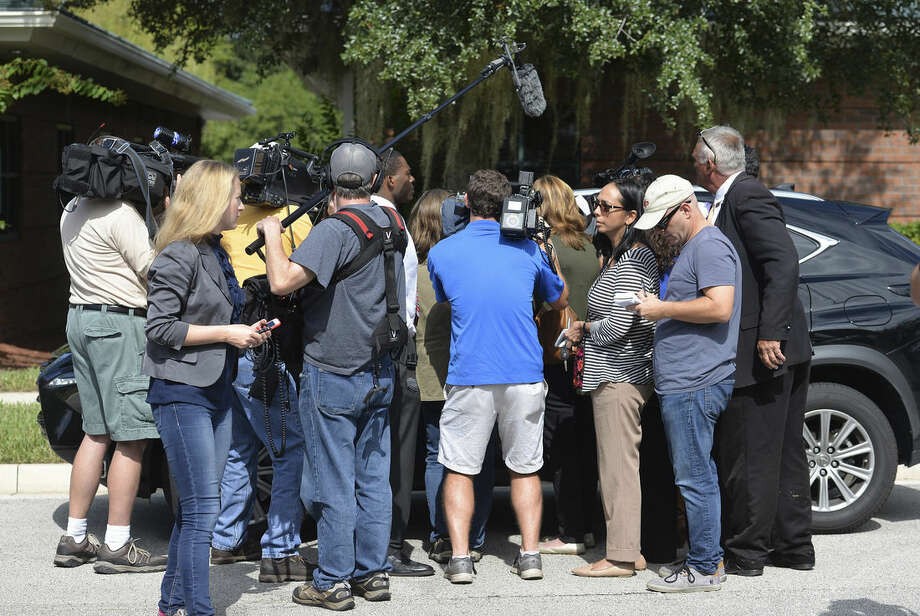 The car of Terrence Meadows, a merchant marine, is surrounded by the press Monday, Sept. 5, 2015, as he stops to answer questions on his way to the Seafarer's International Union hall, in Jacksonville, Fla., to show support for the family and crew of the El Faro. The Coast Guard said Monday that the El Faro, a U.S. cargo ship carrying 33 people that has been missing since it encountered high winds and heavy seas from Hurricane Joaquin, sank and one body was found, but planes and ships will continue searching for the missing crew. (Bruce Lipsky/Florida Times-Union via AP)