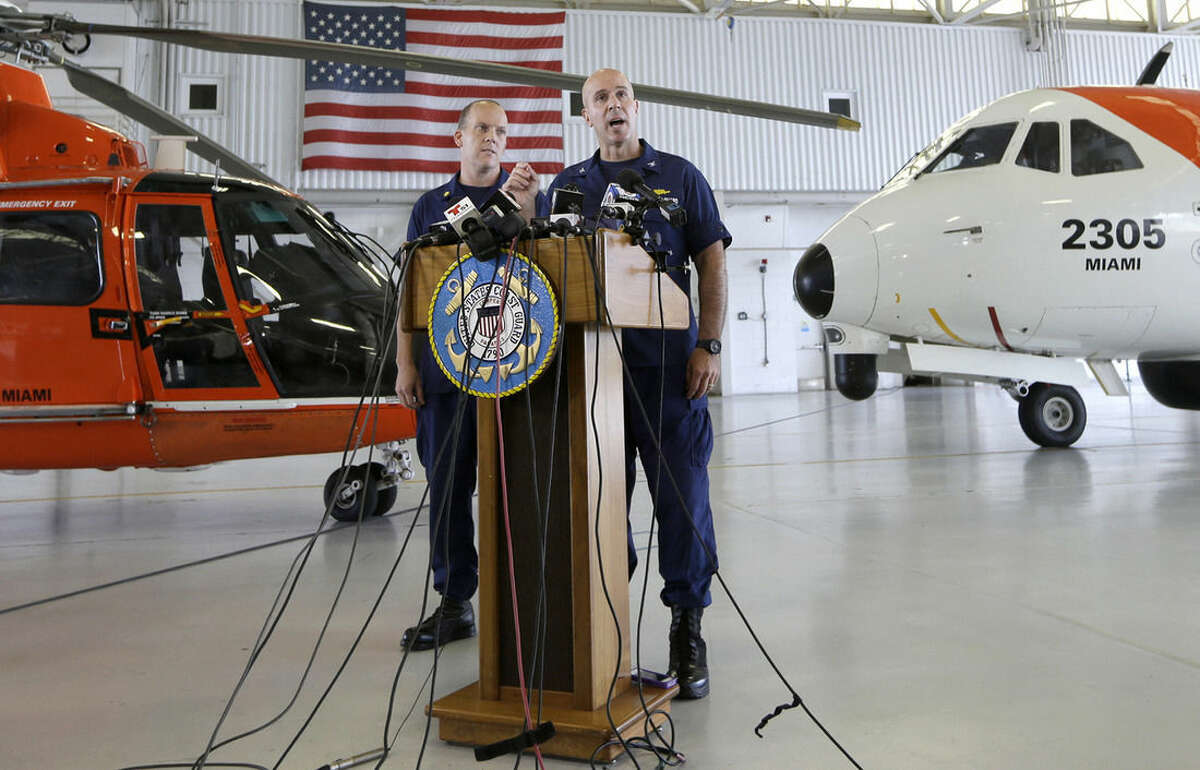Capt. Mark Fedor, right, chief of response for the Coast Guard 7th District, talks to during a news conference as Lt. Commander Gabe Somma, left, listens, Monday, Oct. 5, 2015, at the Opa-locka Airport in Opa-locka, Fla. The Coast Guard said Monday that a U.S. cargo ship carrying 33 people that has been missing since it encountered high winds and heavy seas from Hurricane Joaquin sank and one body was found, but planes and ships will continue searching for the missing crew. (AP Photo/Alan Diaz)