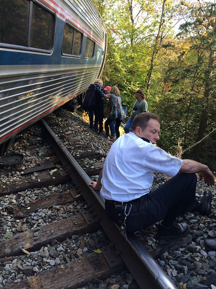 In this photo provided by Brian Bell, a train conductor sits next to an Amtrak train after it derailed, Monday, Oct. 5, 2015, near Roxbury, Vt., about 20 miles southwest of Montpelier, Vt. The train, the Vermonter, was headed from Vermont to Washington, D.C., when it apparently struck rocks that were on the tracks. No life-threatening injuries were reported. (Cathy Bell/Courtesy of Brian Bell via AP) MANDATORY CREDIT