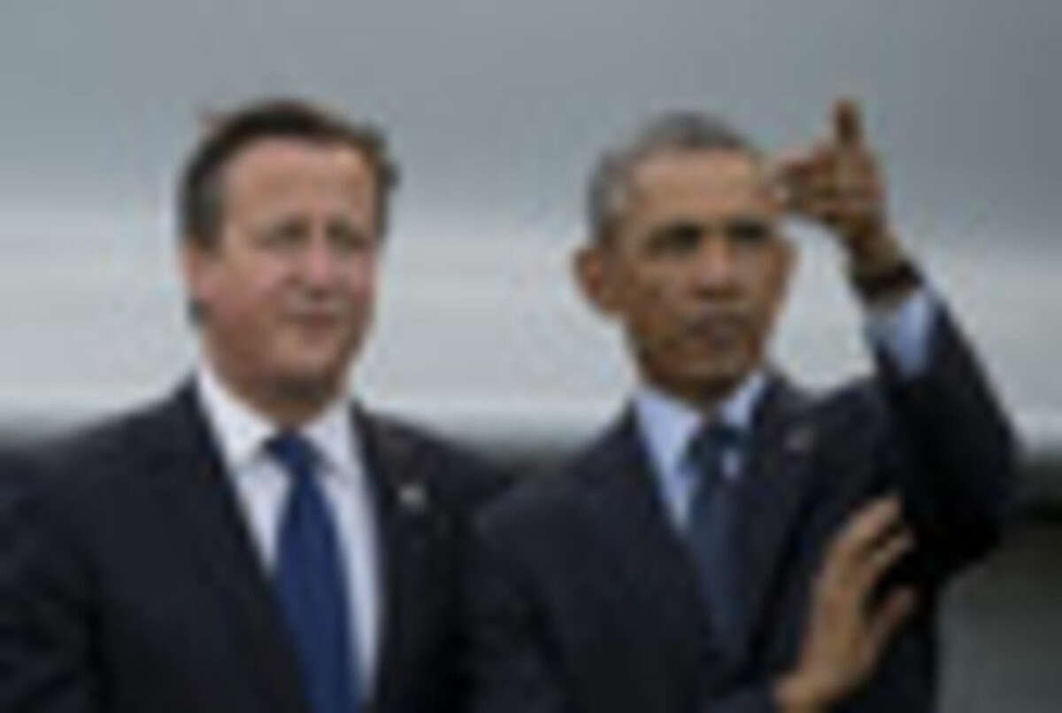 U.S. President Barack Obama, right, stands alongside British Prime Minister David Cameron during a flypast at the NATO summit at the Celtic Manor Resort in Newport, Wales on Friday, Sept. 5, 2014. (AP Photo/Jon Super)