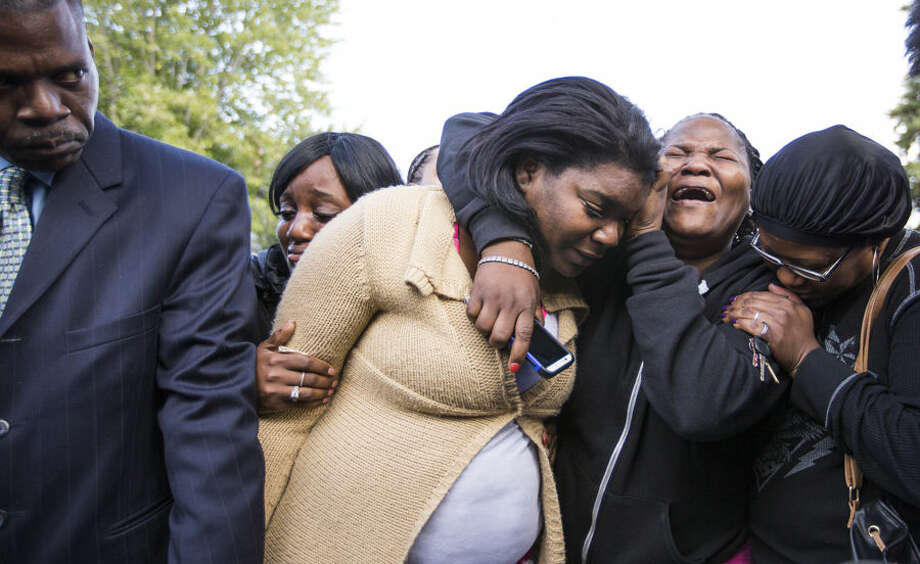 CORRECTS NAME TO TANEISHA STEWART, NOT TANISHA PARKER - Taneisha Stewart, center, the mother of three children who perished in a house fire the night before, cries with her mother, Jackie Cage, and Charlotte Fikes during a prayer vigil outside Parker's home Sunday, Oct. 4, 2015, in Minneapolis. (Leila Navidi/Star Tribune via AP) MANDATORY CREDIT; ST. PAUL PIONEER PRESS OUT; MAGS OUT; TWIN CITIES LOCAL TELEVISION OUT