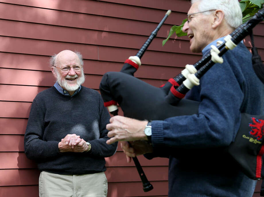 Scientist William C. Campbell, left, smiles as he is serenaded by neighbor John Truman, a bagpipe player with Clan MacPherson, outside his home in North Andover, Mass., Monday, Oct. 5, 2015. Campbell is one of three scientists from the U.S., Japan and China who won the Nobel Prize in medicine on Monday for discovering drugs to fight malaria and other tropical diseases that affect hundreds of millions of people every year. (AP Photo/Mary Schwalm)