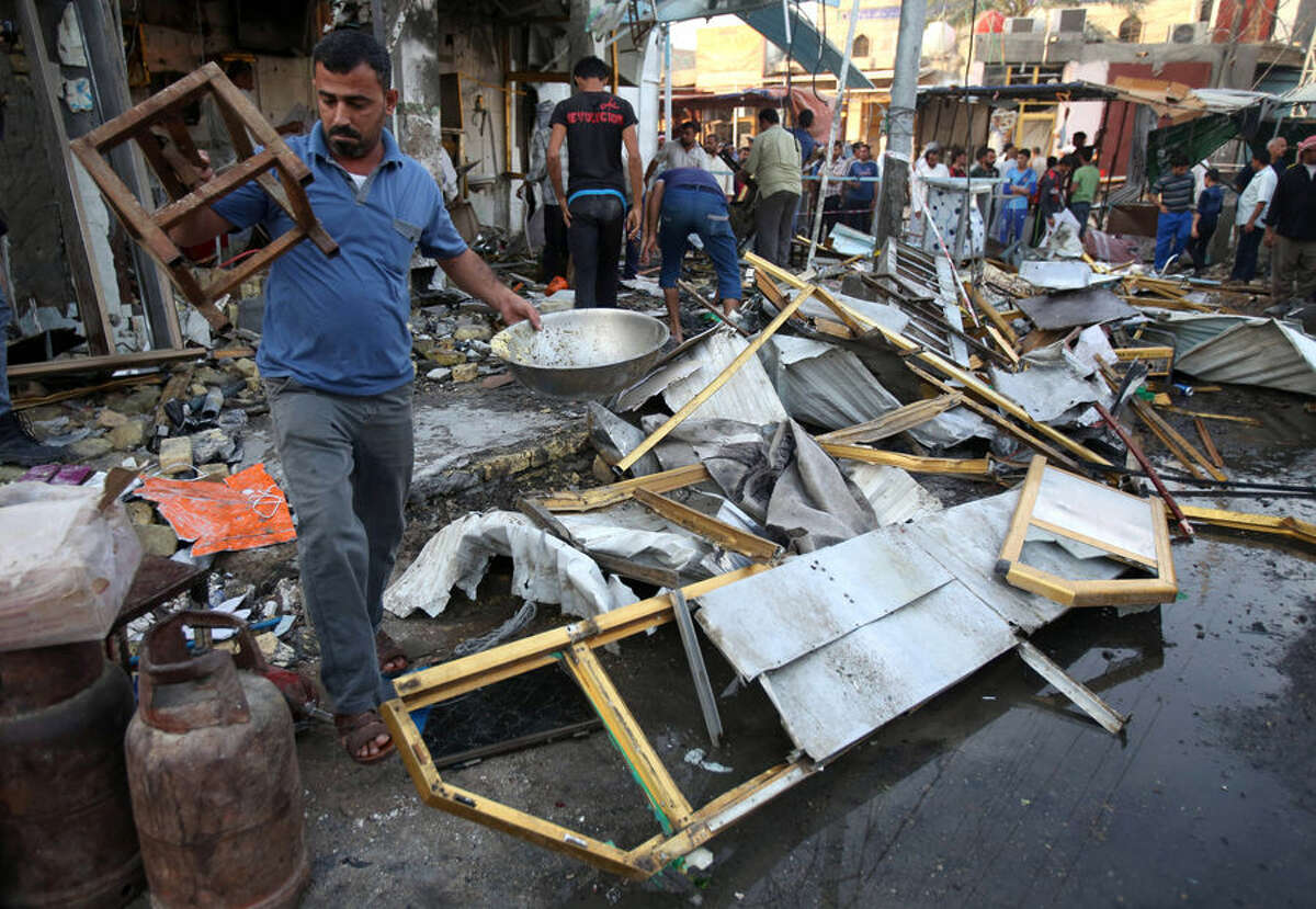 Shop owners clean up debris and inspect the aftermath of a deadly car bomb explosion in a busy commercial district of al-Zubair, a suburb of the predominantly Shiite city of Basra, 340 miles (550 kilometers) southeast of Baghdad, Iraq, Tuesday, Oct. 6, 2015. Iraqi officials say a series of car bombings across Iraq Monday killed and wounded dozens of people. The Islamic State group has claimed responsibility for the car bombing in al-Zubair that killed at least 10 people on Monday. (AP Photo/Nabil al-Jourani)