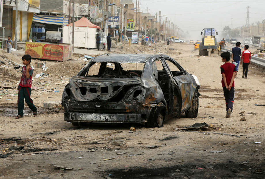 Civilians inspect the aftermath of a car bomb explosion in Husseiniya, about 13 miles (20 kilometers) northeast of Baghdad, Iraq, Tuesday, Oct. 6, 2015. Iraqi officials say a series of car bombings across Iraq Monday killed and wounded dozens of people. (AP Photo/ Karim Kadim)