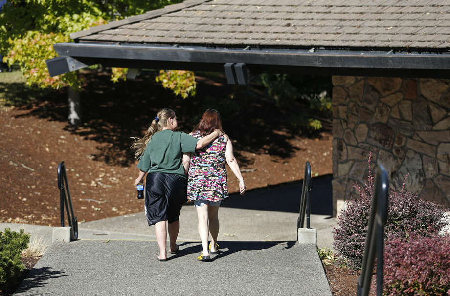 People walk on a path at Umpqua Community College, Monday, Oct. 5, 2015, in Roseburg, Ore. The campus reopened on a limited basis for faculty and students for the first time since armed suspect Chris Harper-Mercer killed multiple people and wounded several others on Thursday before taking his own life at Snyder Hall. (AP Photo/John Locher)