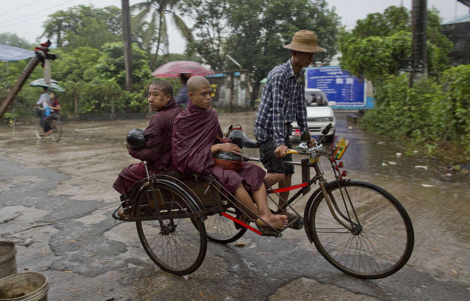 Buddhist monks travel in a rickshaw to collect alms in the rain following a clerics rule of no footwear nor use of umbrellas in Hlaing Tharyar, suburbs of Yangon, Myanmar, Tuesday, Oct. 6, 2015. Downpours during the monsoon season are intense, and often more than 100 millimeters (3.9 inches) of rain falls in an hour resulting in flash floods and traffic jams. (AP Photo/Gemunu Amarasinghe)