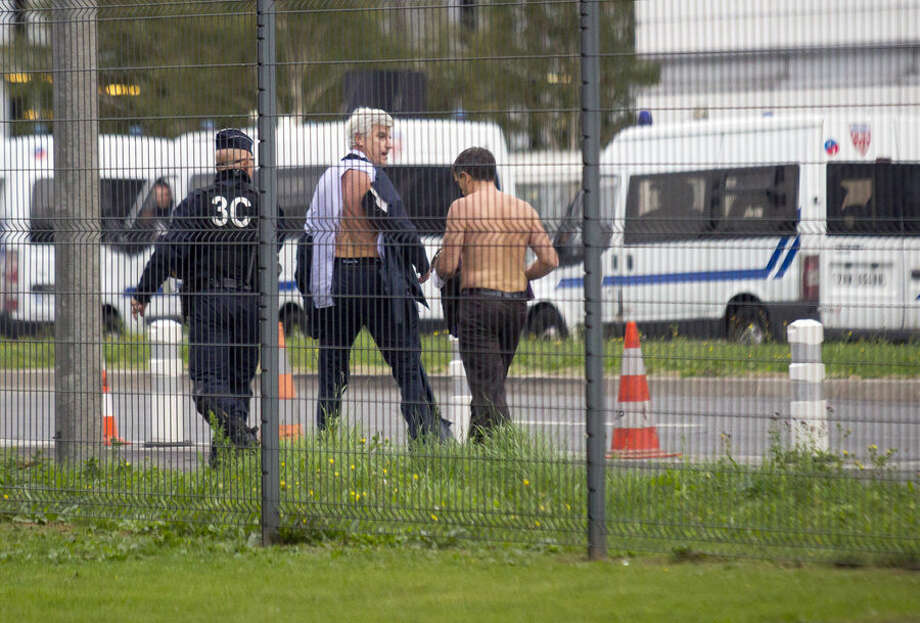 Air France director of Human Ressources, Xavier Broseta, right, and Air France assistant director long-haul flight, Pierre Plissonnier, center, are protected by a police officer as they flee Air France headquarters at Roissy Airport, north of Paris, after scuffles with union activist, Monday, Oct. 5, 2015. Union activists protesting proposed layoffs at Air France stormed the headquarters during a meeting about the job cuts, zeroing in on two managers who had their shirts torn from their bodies, scaled a fence and fled under police protection. (AP Photo/Jacques Brinon)