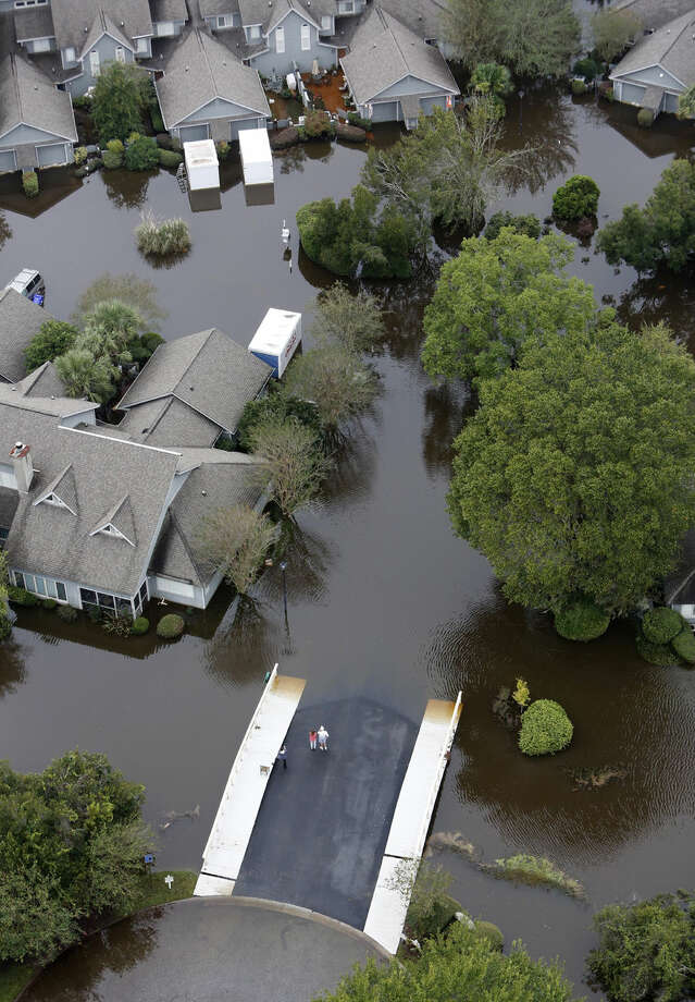 People stand on the safety of a bridge as homes sit in floodwater in a subdivision west of the Ashley river in Charleston, S.C., Monday, Oct. 5, 2015. The Charleston and surrounding areas are still struggling with floodwaters due to a slow moving storm system. (AP Photo/Mic Smith)