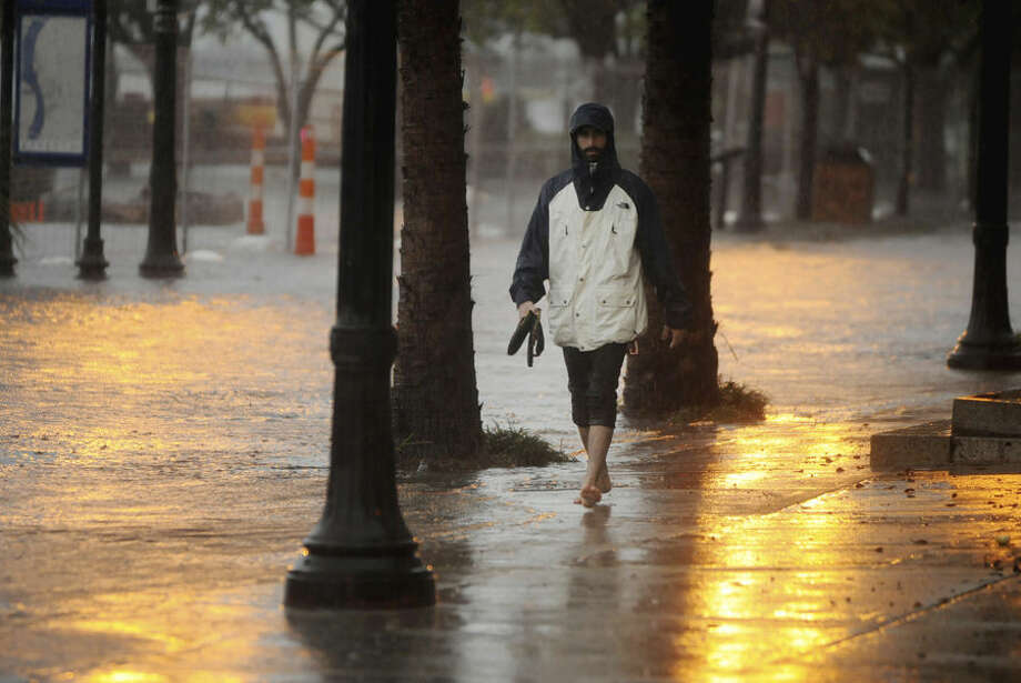 Zach Stadelman walks along a flooded street in Wilmington, N.C., Sunday, Oct. 4, 2015. Numerous roads in Brunswick and New Hanover counties in southeastern North Carolina are impassable as a storm system that inundated South Carolina moves north. (Mike Spencer/The Star-News via AP) MANDATORY CREDIT