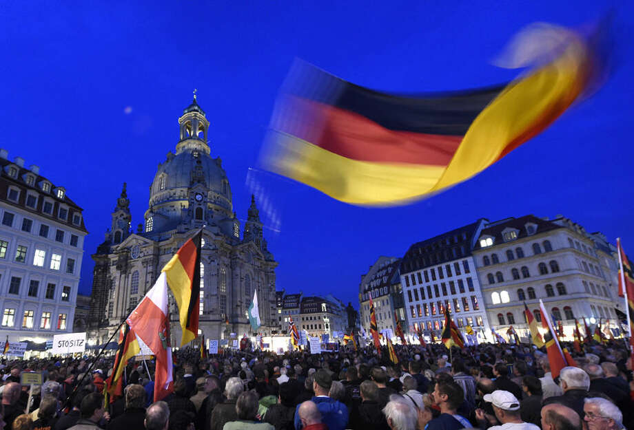 Protestors wave a German flag in front of the Church of Our Lady during a demonstration of PEGIDA (Patriotic Europeans against the Islamization of the West) in Dresden, eastern Germany, Monday, Oct. 5, 2015. (AP Photo/Jens Meyer)