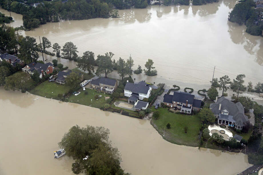 Floodwaters close in on homes on a small piece of land on Lake Katherine in Columbia, S.C., Monday, Oct. 5, 2015. After a week of steady rain, the showers tapered off Monday and an inundated South Carolina turned to surveying a road system shredded by historic flooding. (AP Photo/Chuck Burton)