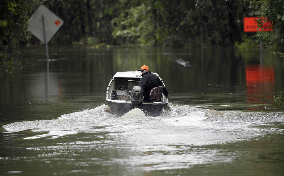 Hunter Baker drives his boat down a flooded East Black Creek Road to his home following heavy rains in Florence, S.C., Monday, Oct. 5, 2015. Flooding continues throughout the state following record rainfall amounts over the last several days. (AP Photo/Gerry Broome)