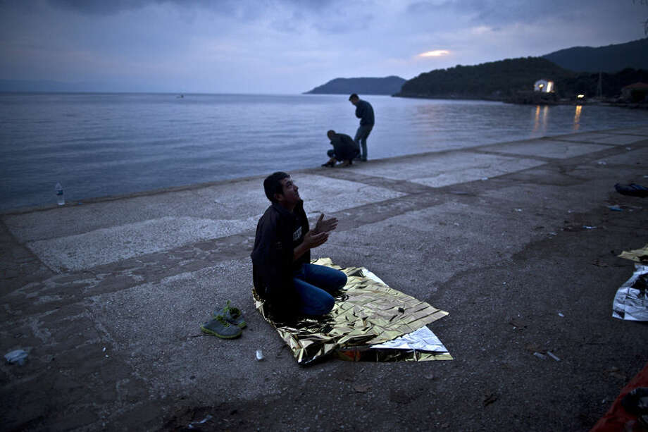 An Afghan refugee offers early morning prayers on a roadside as he and others spent the night at a resting point after arriving on a dinghy from the Turkish coast to the northeastern Greek island of Lesbos, Tuesday, Oct. 6 , 2015. (AP Photo/Muhammed Muheisen)
