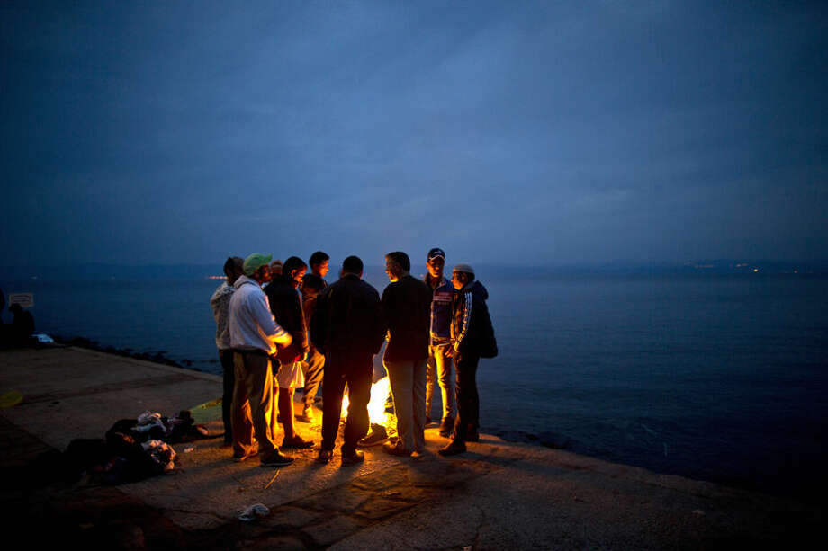Afghan refugees gather around a fire to warm themselves from the early morning cold, after spending the night at a resting point, after arriving on a dinghy from the Turkish coast to the northeastern Greek island of Lesbos, Tuesday, Oct. 6 , 2015. (AP Photo/Muhammed Muheisen)