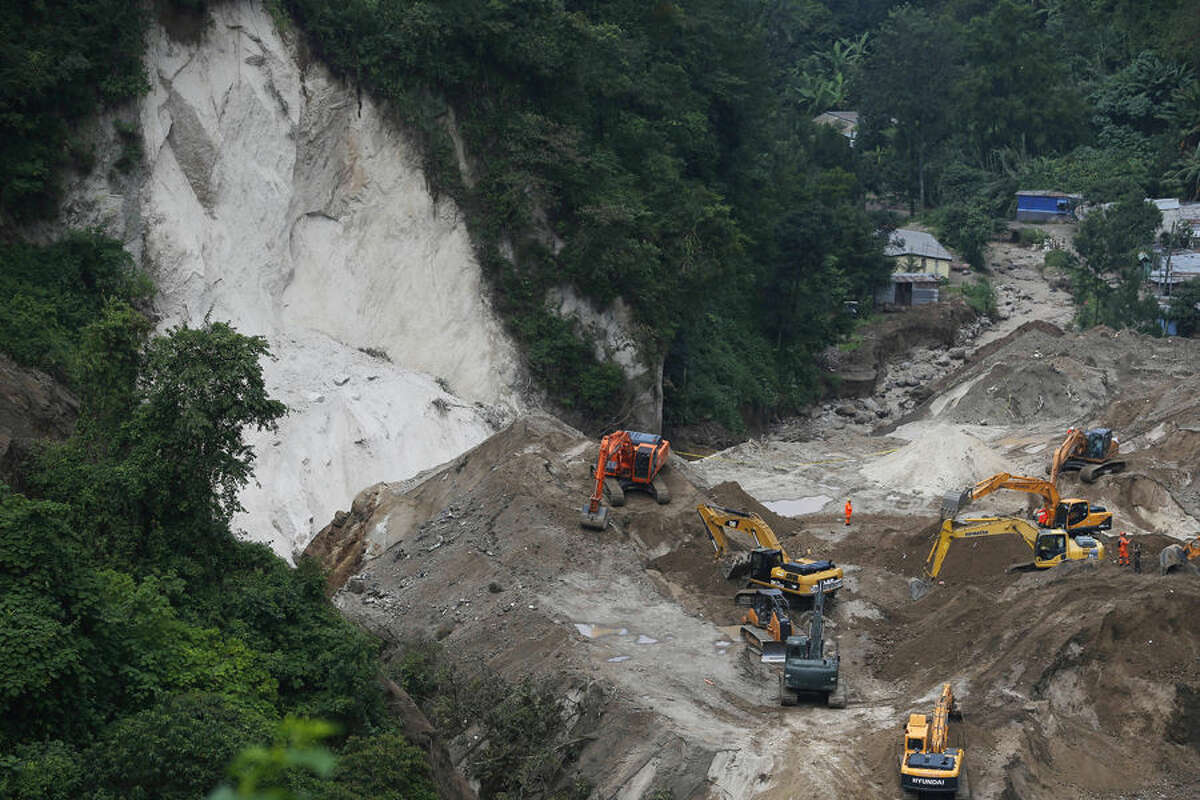 Bulldozers move land for a fourth day to search for victims of a fatal mudslide, amid new, smaller slides in Cambray, a neighborhood in the suburb of Santa Catarina Pinula, on the outskirts of Guatemala City, Monday, Oct. 5, 2015. Hope faded for many families that they would find survivors, as the smell of rotting bodies spread across the enormous mound of earth, and rescuers reported the buried dwellings they reached were filled with water, suggesting anyone trapped inside would have drowned. (AP Photo/Moises Castillo)