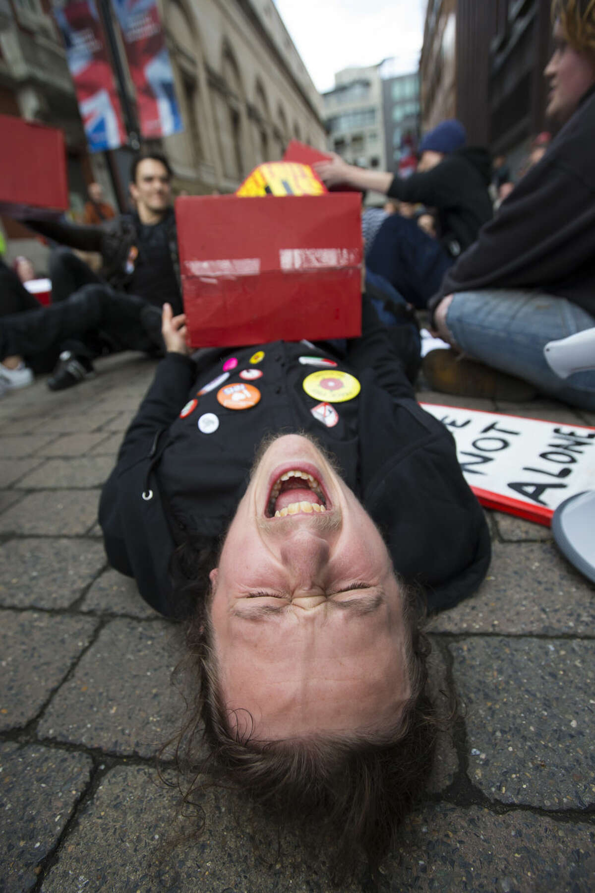 An anti-austerity protestor reacts as he lies on the ground, joining about 150 protesters demonstrating outside Britain's Conservative Party Conference, Manchester, England, Monday Oct. 5, 2015. The ruling Conservative Party continue their annual conference on Monday, seemingly buoyant after their electoral triumph in May. (AP Photo/Jon Super)