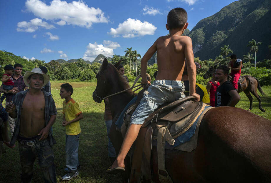 """People wait the start of the """"sortija"""" horseback competition in La Sierra neighborhood of La Palma, Pinar del Rio, Cuba, Saturday, Oct. 3, 2015. In rural municipalities such as La Palma, cultural councils have been promoting the revival of these rich and varied celebrations. (AP Photo/Ramon Espinosa)"""