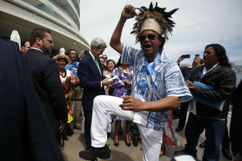 A man from Easter Island dances as U.S. Secretary of State John Kerry, behind, is given an Easter Island flag on the sidelines of the Our Ocean international conference on marine protection in Vina del Mar, Chile, Monday, Oct. 5, 2015. President Barack Obama declared new marine sanctuaries in Lake Michigan and the tidal waters of Maryland on Monday, while Chile blocked off a vast expanse of the Pacific Ocean near the world-famous Easter Island from commercial fishing and oil and gas exploration. (AP Photo/Luis Hidalgo)