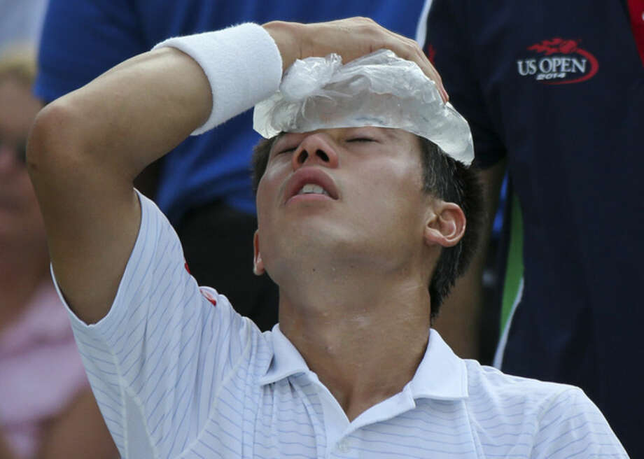 Kei Nishikori, of Japan, applies an ice pack to his forehead to cool down during a break between games against Stan Wawrinka, of Switzerland, during the quarterfinals of the 2014 U.S. Open tennis tournament, Wednesday, Sept. 3, 2014, in New York. (AP Photo/Mike Groll)