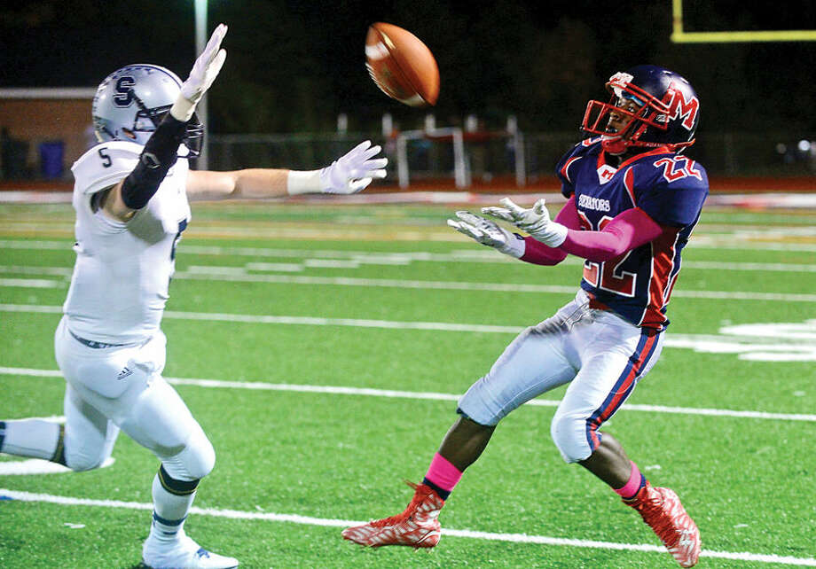 Hour photo / Erik Trautmann #22 for Brien McMahon High School, Tyquan Samuel, pulls in a long reception,l during their game against Staples Friday night in Norwalk.