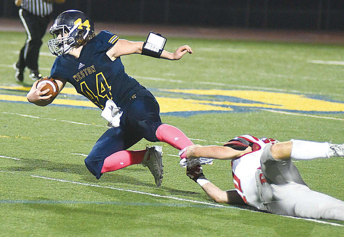 Hour photo/John Nash Weston's Bobby Lummis, left, gets pulled down by the foot by Pomperaug tackler Austin Post during Friday's game at Weston.