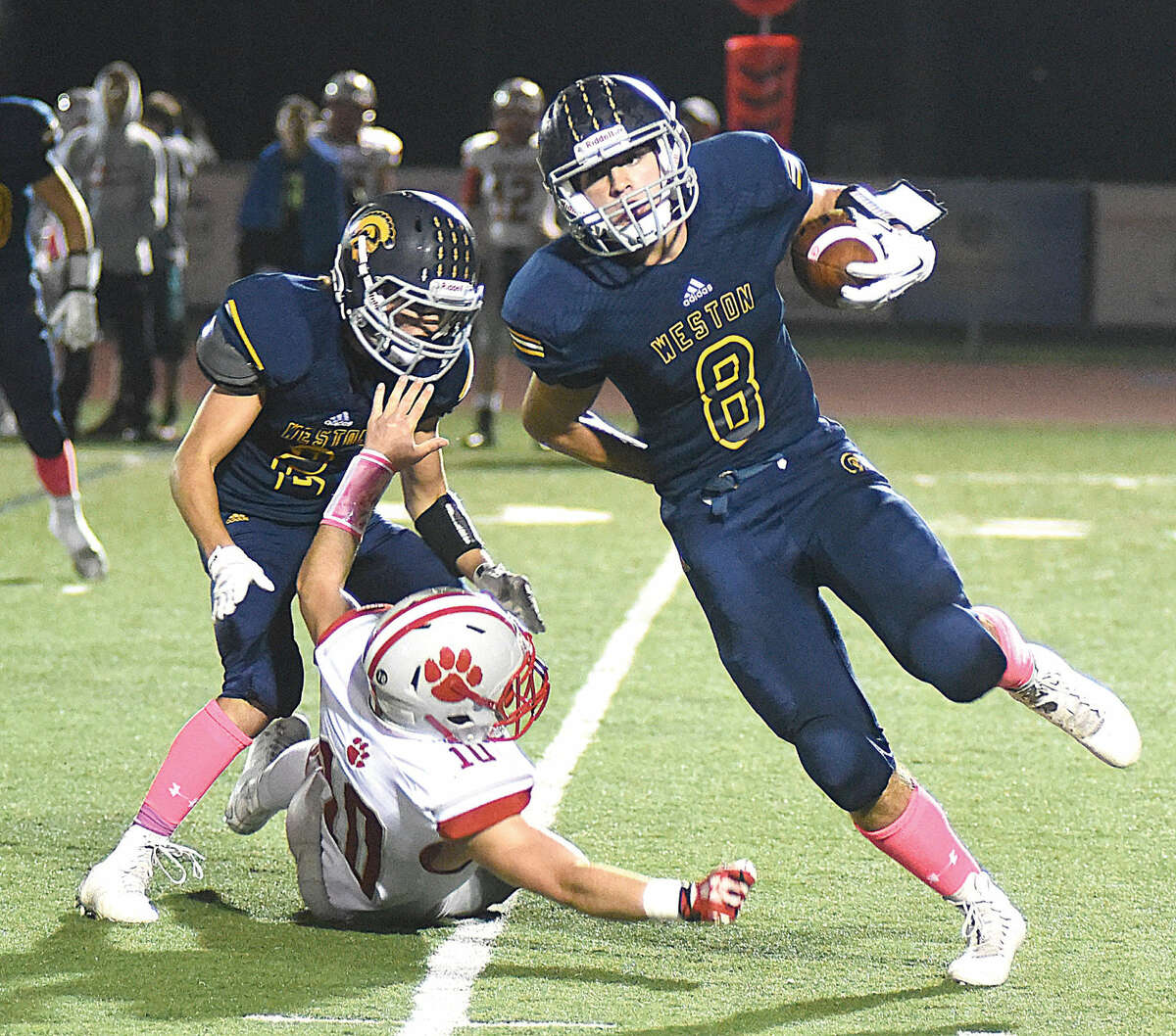 Hour photo/John Nash Weston's Jason Lawrence (8)avoids the tackle of Pomperaug's Austin Post during Friday night's game in Weston.