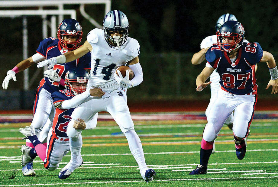 Hour photo / Erik Trautmann #14 for Staples High School, Sam Arciola, tries to escape defensive back Jack Coulter during their football game against Brien McMahon in Norwalk Friday night.