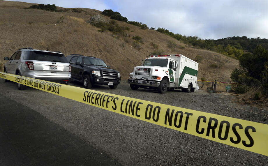 In this Tuesday, Oct. 6, 2015 photo, Marin County Sheriff's Office personnel investigate a homicide near the top of White's Hill on Old Railroad Grade near Fairfax, Calif. A tantra teacher who made DVDs on yoga for lovers and taught classes at a clothing-optional retreat was found shot to death on a hiking trail in Northern California, still holding onto the leash of his wounded dog, authorities said. Detectives are looking for three people of interest in the killing of Steve Carter, 67.(Robert Tong/Marin Independent Journal via AP)