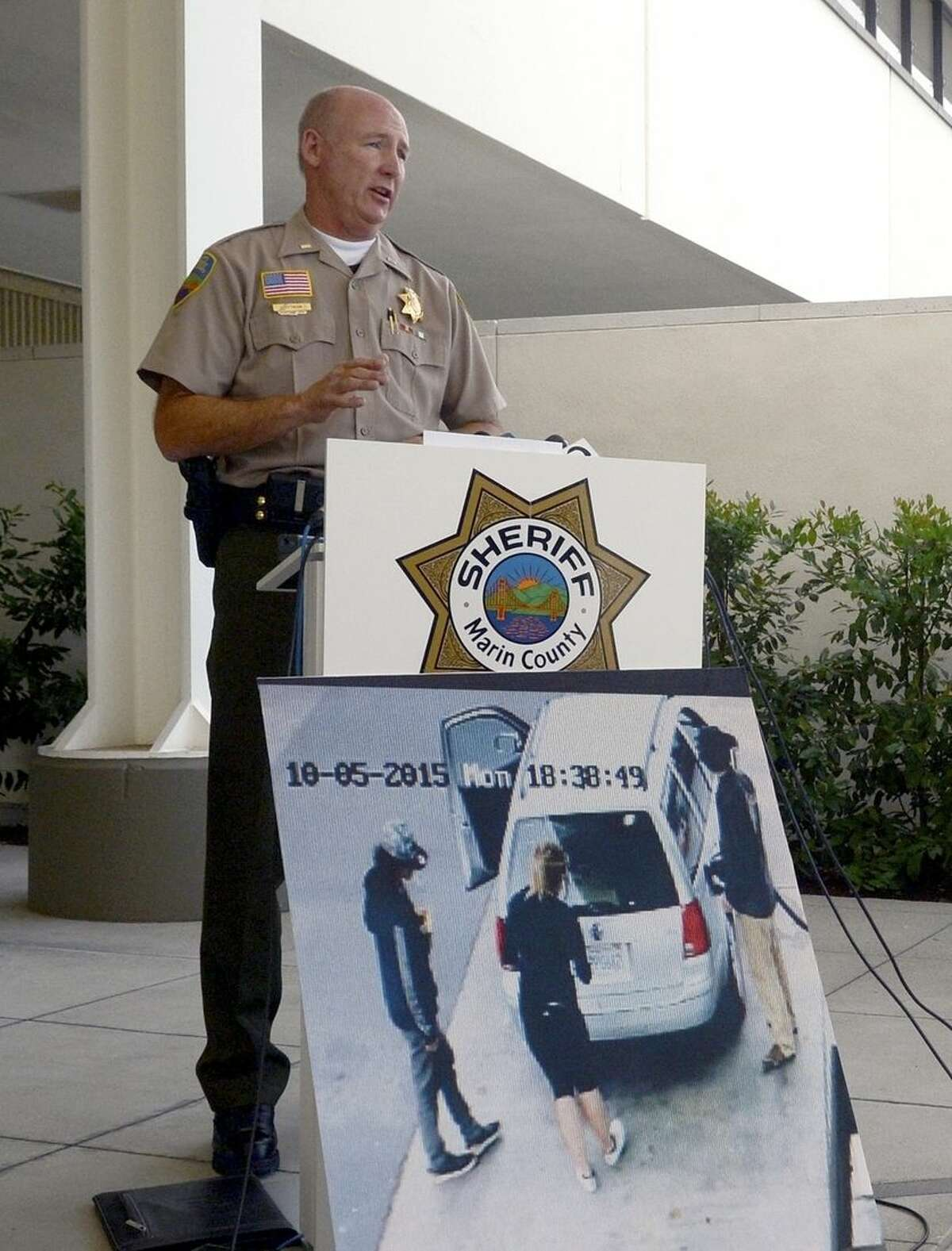 Lt. Doug Pittman of the Marin County Sheriff's office speaks during a news conference regarding the death of 67-year-old yoga teacher Steve Carter, in San Rafael, Calif., Wednesday, Oct. 7, 2015. Three people have been arrested in the killing of a California yoga teacher who was shot on a trail in what appeared to be a random crime while walking his dog, authorities said Wednesday. The three people taken into custody in Portland, Oregon were described as drifters and a motive was unknown. The photograph in the foreground, from a gas station surveillance camera, shows two men and one woman around the victim's car in Pt. Reyes Station, Calif. (Alan Dep/Marin Independent Journal via AP)