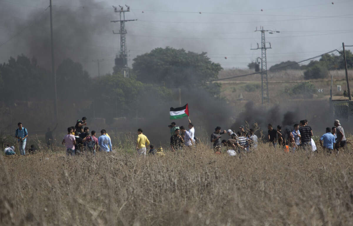 Palestinian protesters gather during clashes with Israeli soldiers on the Israeli border Eastern Gaza City, Friday, Oct. 9, 2015. At least four attacks - three by Palestinians and one by an Israeli - as well as deadly clashes along the Gaza border threatened to escalate tensions throughout the country on Friday as Israel struggled to control spiraling violence. (AP Photo/ Khalil Hamra)