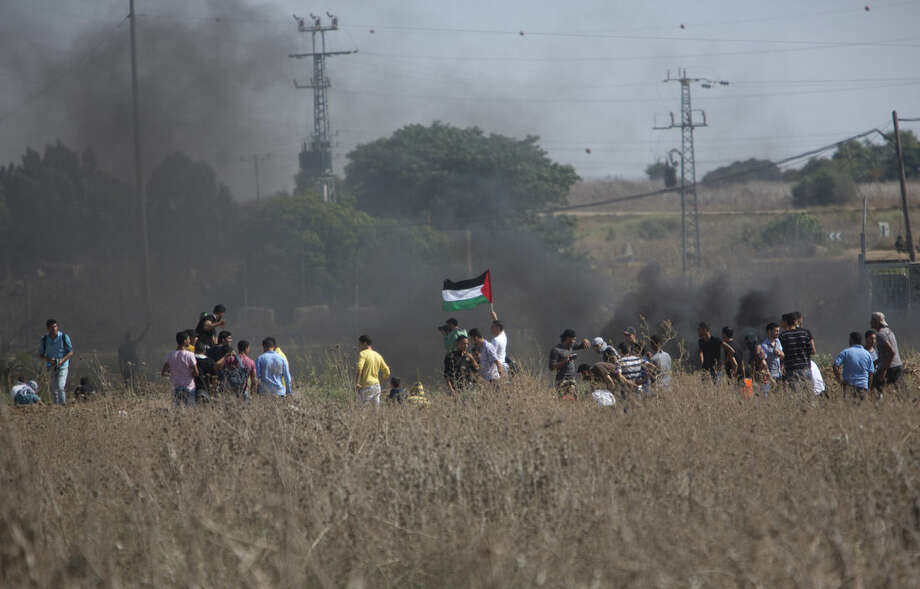 Palestinian protesters gather during clashes with Israeli soldiers on the Israeli border Eastern Gaza City, Friday, Oct. 9, 2015. At least four attacks — three by Palestinians and one by an Israeli — as well as deadly clashes along the Gaza border threatened to escalate tensions throughout the country on Friday as Israel struggled to control spiraling violence. (AP Photo/ Khalil Hamra)