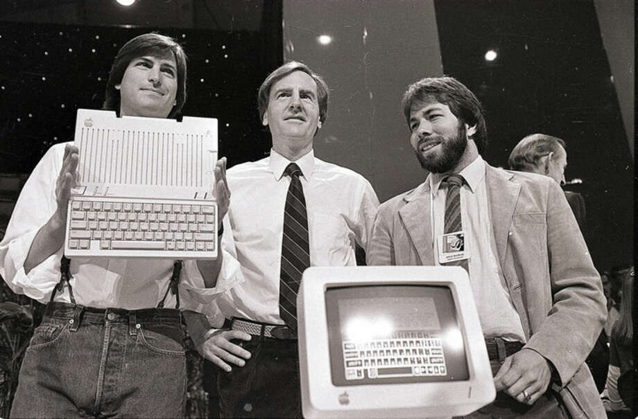 """FILE - In this April 24, 1984 file photo, Steve Jobs, left, chairman of Apple Computers, John Sculley, center, president and CEO, and Steve Wozniak, co-founder of Apple, unveil the new Apple IIc computer in San Francisco. """"Steve Jobs,"""" released Friday, Oct. 9, 2015, is the latest movie to examine a charismatic visionary who mesmerized the masses with his trendsetting gadgets while alienating his subordinates and friends with an almost-inhumane cruel streak. The story is told through Jobs' interactions with six central figures in his life: his former marketing chief, Joanna Hoffman; his former girlfriend Chrisann Brennan; Apple co-founder and friend Wozniak; former Apple engineer Andy Hertzfeld; former Apple CEO Sculley; and Lisa, the daughter that Jobs refused to acknowledge for many years. (AP Photo/Sal Veder, File)"""