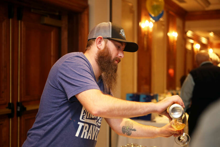 Ryan Crowley from Two Roads Brewery fills a glass during the Norwalk Police Activies League's Beer Tasting at the Norwalk Inn Thursday evening. Hour Photo / Danielle Calloway