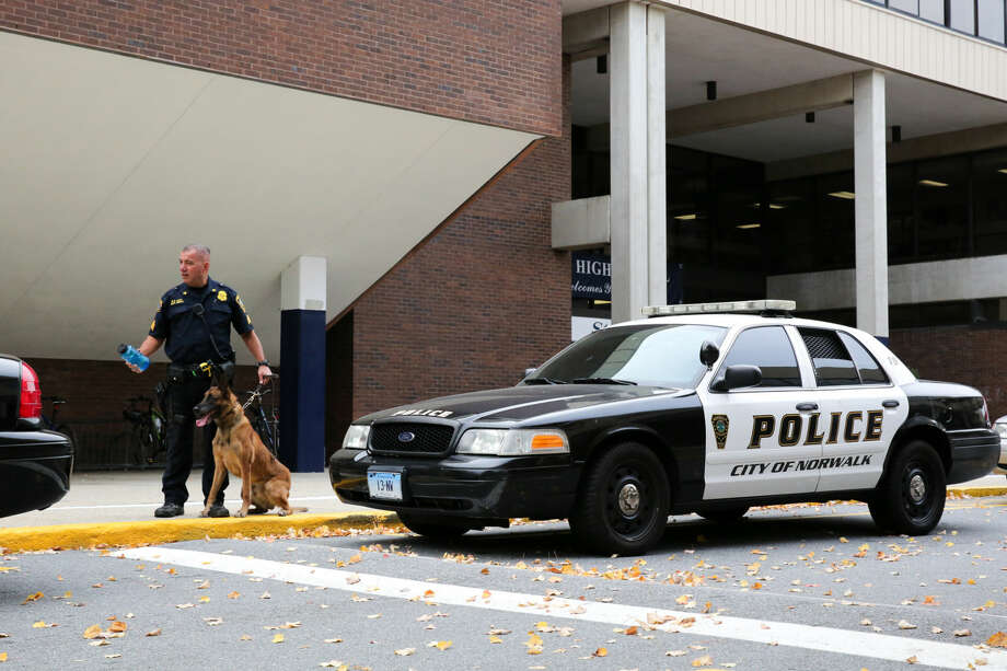 Hour photo/Chris Palermo Sgt. Reda of the Norwalk Police Departments holds his K-9 unit outside of Wilton High School during the illegal drug search Friday morning.