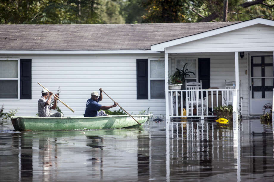 Arthur Holmes and Carnell Linen row a boat to get items from a flooded home in the Dunbar community of Georgetown, S.C., Friday, Oct. 9, 2015. A week after the heavy rains first began, some South Carolina residents are still evacuating and others are stacking up sandbags for more possible flooding even as the nation's top security official prepares to inspect the damage firsthand. (Jason Lee/The Sun News via AP) LOCAL PRINT OUT (MYRTLE BEACH HERALD OUT, HORRY INDEPENDENT OUT, CAROLINA FOREST CHRONICLE, GEORGETOWN TIMES OUT); MANDATORY CREDIT