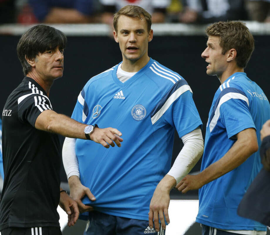 Gemany's head coach Joachim Loew , left, talks to Manuel Neuer, center, and Thomas Mueller during an open training session ahead of the friendly soccer match between Germany and Argentina on Wednesday in Duesseldorf, Germany, Monday, Sept. 1, 2014. (AP Photo/Frank Augstein)