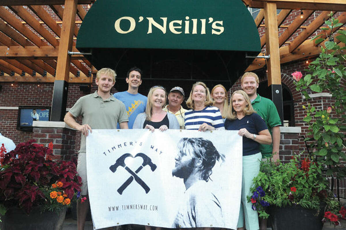 Family members who organized the Timmer's Way Music Festival stand in front of O'Neill's Pub & Restaurant in Norwalk. Pictured from left: Steve Wood, Dave Ferrell, Shelly Ferrell, Tim Wood, Robin Wood, Kristin Woods, Jane Wood and Mike Wood.
