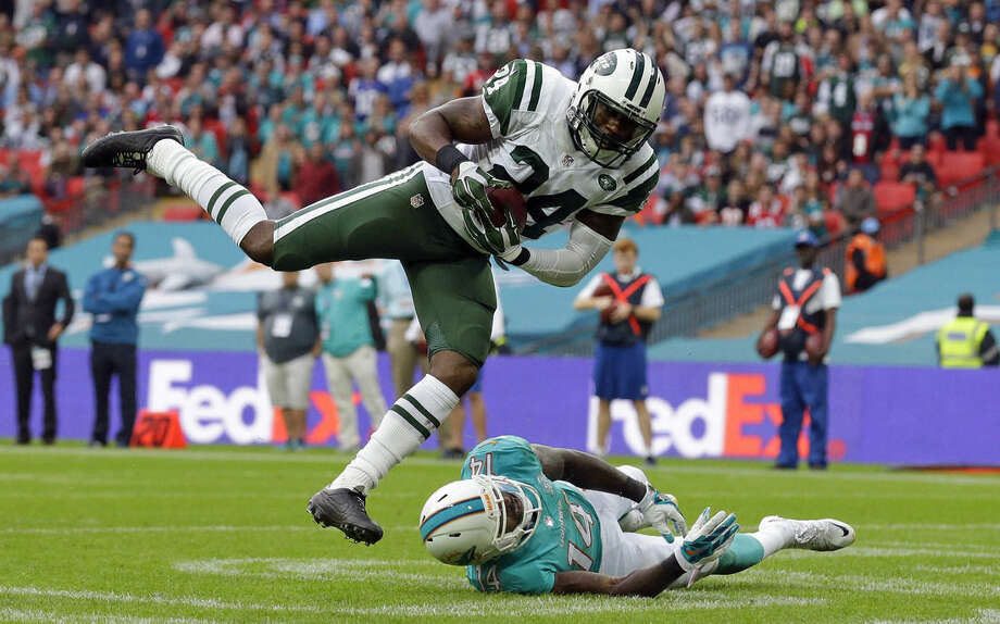 New York Jets' Darrelle Revis makes an interception over Miami Dolphins' Jarvis Landry during the NFL football game between the New York Jets and the Miami Dolphins and at Wembley stadium in London, Sunday, Oct. 4, 2015. (AP Photo/Matt Dunham)