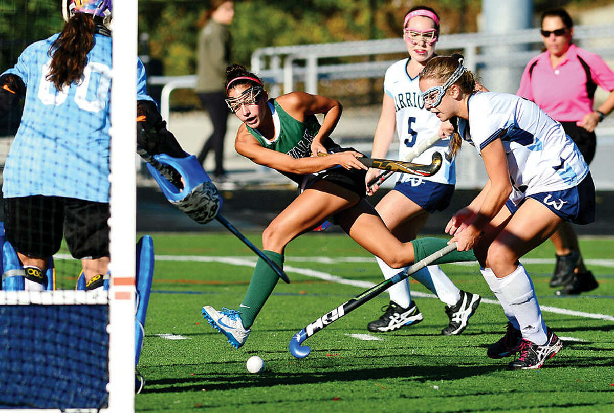 Hour photo / Erik Trautmann The Norwalk High School's Marissa Mastrinni takes a shot on goal as Mary Thomas and Meredith Rappaport try to defend during their field hockey at Fujitani Stadium Saturday.