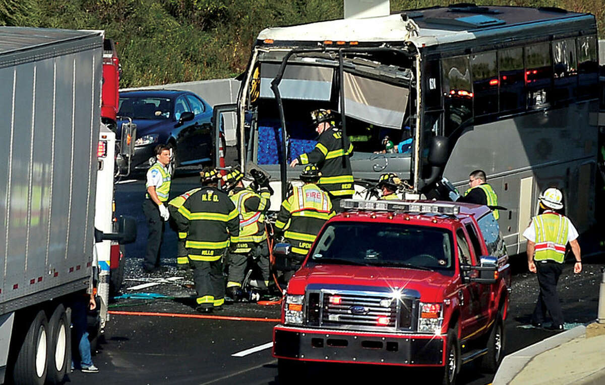 Hour photo / Erik Trautmann Norwalk firefighter look to free the driver of a coach bus that was trapped after his bus collided with a tractor trailer at exit 15 on I-95 Southbound Wednesday afternoon.