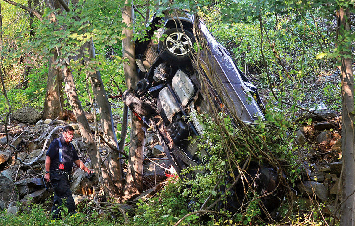 Hour photo / Erik Trautmann Emergency personnel investigate a four car accident that closed down Route 7 Southbound late Tuesday afternoon. Several cars overturned sending one down the over the guardrail and down the Norwalk River embankment.