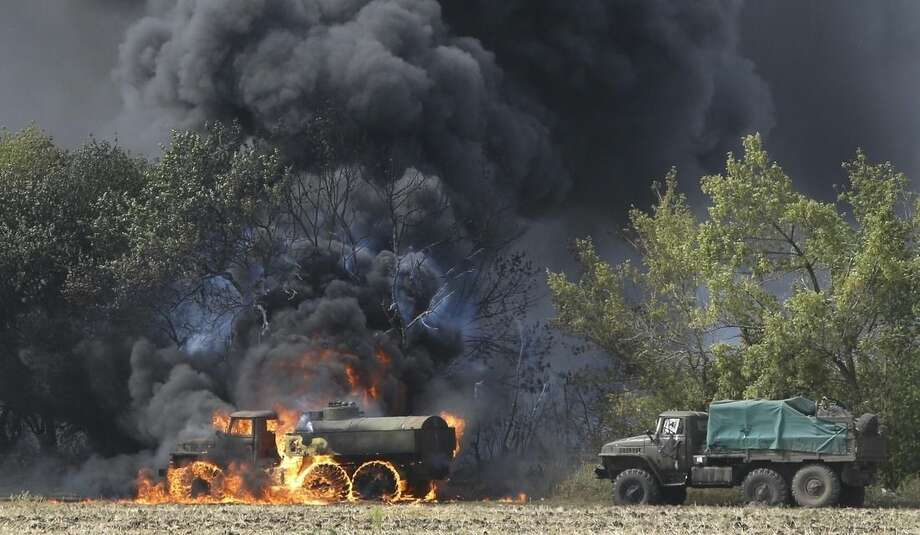 Unmarked Military vehicles burning in country roads in the village of Berezove, eastern Ukraine, Thursday, Sept. 4, 2014, after a clash between pro-government troops and Russian-backed separatist militia. Separatist rebels have made major strides in their offensive against Ukrainian government forces in recent days, drawing on what Ukraine and NATO says is ample support from the Russian military. (AP Photo/Sergei Grits)