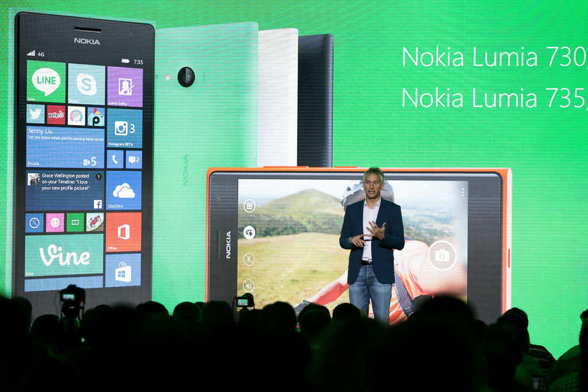 Chris Weber, CVP, Mobile Devices Sales of Microsoft presents the new Lumia 730 and 735 smart phones during his keynote speech at a Microsoft Nokia presentation event at the consumer electronic fair IFA in Berlin, Thursday, Sept. 4, 2014. (AP Photo/Markus Schreiber)