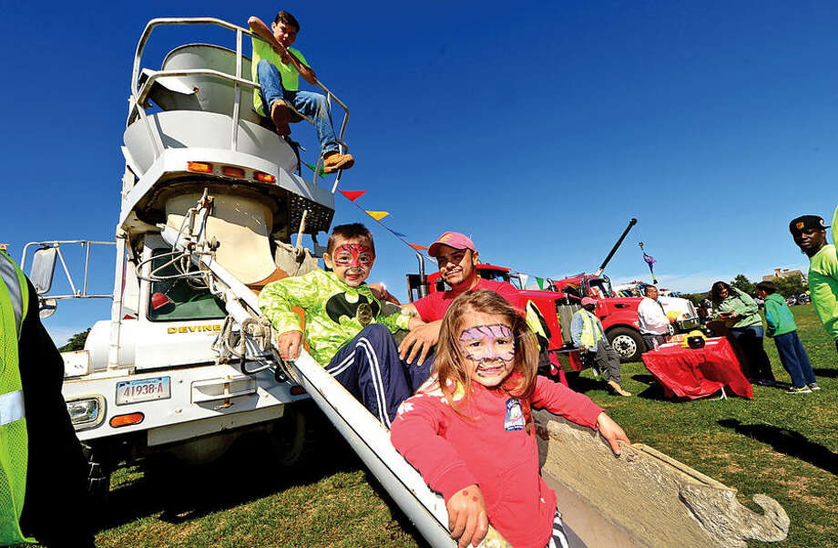 Hour photo / Erik Trautmann Cole and Kiely Dewey, 4 and 3, enjoy riding in Devine Bros. cement truck shoot with the help of DEvine employees Dale Donovan and Will Torres at the Human Services Council's 4th Annual KIDZFEST Touch-A-Truck & More Fundraiser to benefit Children's Connection Saturday, October 10, 2015 at Taylor Farm Park in Norwalk. The hands-on interactive family event featured over 60 vehicles that dig, climb, rescue, crunch, honk and fly.