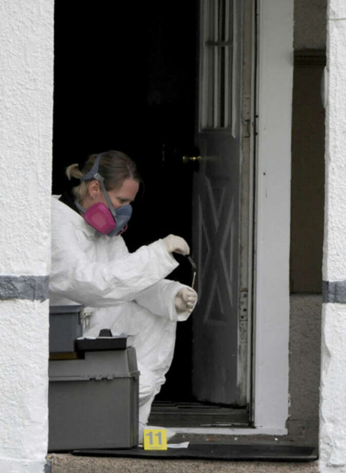 In this photo taken on Tuesday, Sept. 2, 2014, Brenda McNeely collects evidence at a home in Bucyrus, Ohio, where one of four men were found beaten to death Monday. Authorities in the northern Ohio town are asking for the public's help in solving the slayings of four men, between the ages of 50 and 70, who where were found beaten to death in separate homes this week. (AP Photo/News Journal, Daniel Melograna) NO SALES