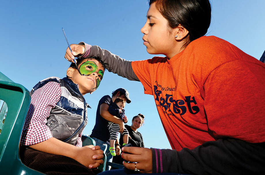 Hour photo / Erik Trautmann Jacob Balenzuela, 4, gets his face painted by volunteer Madeline Cortez-Gomez at the Human Services Council's 4th Annual KIDZFEST Touch-A-Truck & More Fundraiser to benefit Children's Connection Saturday, October 10, 2015 at Taylor Farm Park in Norwalk. The hands-on interactive family event featured over 60 vehicles that dig, climb, rescue, crunch, honk and fly.