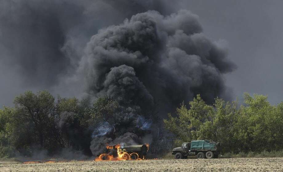 An unmarked military vehicle burns on a country road in the village of Berezove, eastern Ukraine, Thursday, Sept. 4, 2014, after a clash between pro-government troops and Russian-backed separatist militia. Separatist rebels have made major strides in their offensive against Ukrainian government forces in recent days, drawing on what Ukraine and NATO says is ample support from the Russian military. (AP Photo/Sergei Grits)